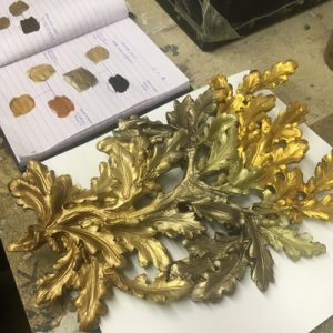 A wall light is painted in a variety of gold colours and notes are taken to determine which is the favourable shade